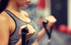 sport, fitness, lifestyle and people concept - close up of young woman flexing muscles on cable gym machine
