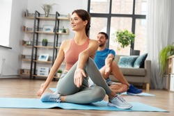 sport, fitness, lifestyle and people concept - smiling man and woman stretching at home