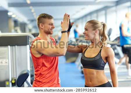 sport, fitness, lifestyle, gesture and people concept - smiling man and woman doing high five in gym #285992612