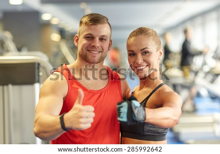 sport, fitness, lifestyle, gesture and people concept - smiling man and woman showing thumbs up in gym