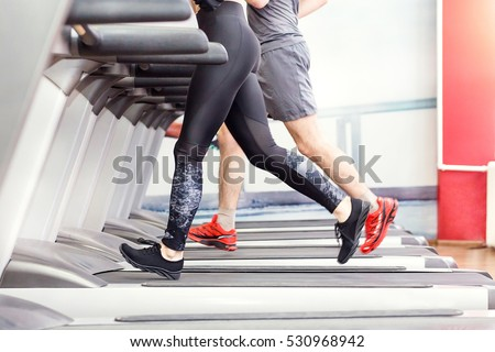 Sport, fitness, lifestyle, technology and people concept - close up of woman and men legs walking on treadmills in the gym.