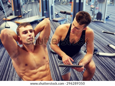 sport, fitness, lifestyle, technology and people concept - man and personal trainer with tablet pc computer and flexing abdominal muscles in gym
