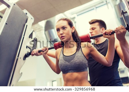 sport, fitness, teamwork, weightlifting and people concept - young woman and personal trainer with barbell flexing muscles in gym