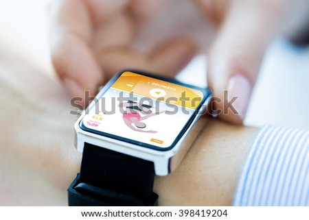 sport, fitness, technology and people concept - close up of woman hands setting smart watch with sports application on screen