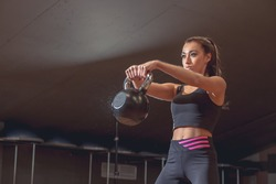 sport, fitness, weightlifting and training concept - group of people with kettlebells and heart-rate trackers exercising in gy