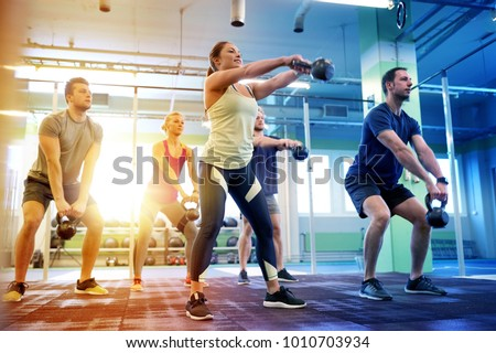 sport, fitness, weightlifting and training concept - group of people with kettlebells exercising in gym #1010703934