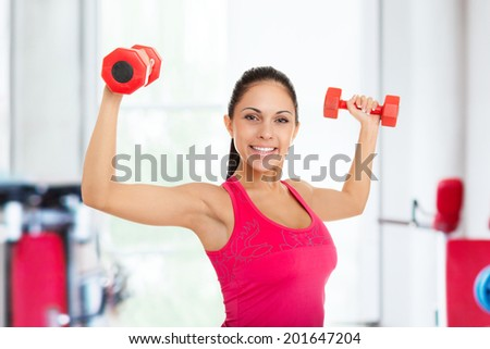sport fitness woman in gym, young healthy girl smile gym exercises dumbbells working out