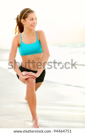 Sport fitness woman training on beach stretching out legs after running or jogging outside. Beautiful young fit multicultural mixed race Caucasian / Asian female fitness model outdoors.