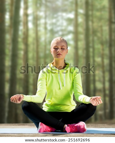 sport, fitness, yoga and people concept - happy young woman meditating in lotus pose and sitting on mat over woods background
