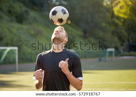 sport, football and people - soccer player playing and juggling ball using header technique on field