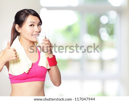 sport girl drinking water and show thumb up after sport with nature green background, model is a asian woman