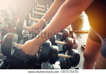 Sport girl holding weight on blurred background of Gym fitness