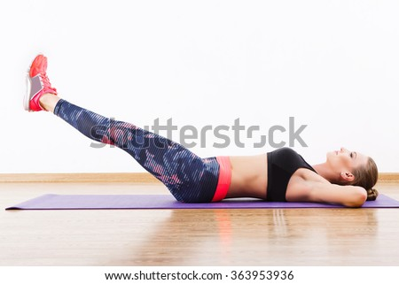 Sport girl with dark hair wearing pink snickers, dark leggings and black short top doing leg raise at gym, fitness, white wall and wooden floor. #363953936