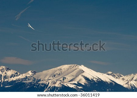 Sport glider flying over high mountains in Italy