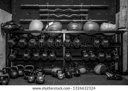 Sport gym equipment for fitness and body building workout training with barbell bars dumbbells kettlebells and balls on the stand black and white hard contrast