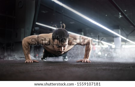 Photo of  Sport. Handsome man doing push ups exercise with one hand in fitness gym.