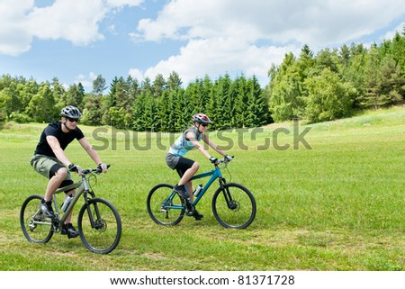 Sport happy couple riding bicycles in countryside meadows