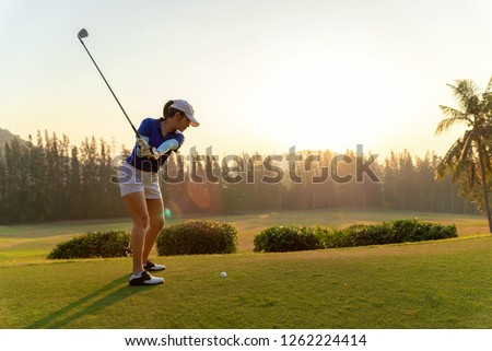 Sport Healthy. Asian sporty women golf player doing golf swing tee off on the green sunset evening time, she presumably does exercise. Healthy and Lifestyle Concept.