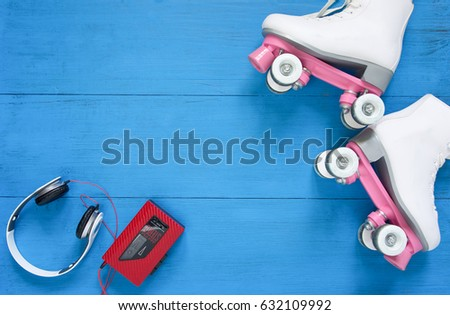 Sport, healthy lifestyle, roller skating background. White roller skates, headphfones and vintage tape player. Flat lay, top view.