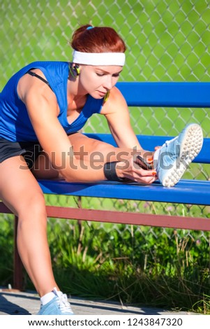 Sport Ideas. Portrait of Concentrated Caucasian Sportswoman in Outdoor Outfit Making Legs Stretching Exercises on Bench And Listening to Music from Smartphone. Vertical Image Composition