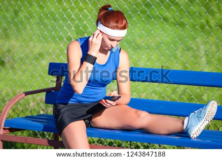 Sport Ideas. Portrait of Relaxing Sportswoman  in Outdoor Outfit Sitting on Bench While Listening to Music from Smartphone. Horizointal Image Composition