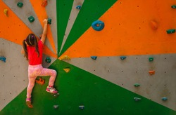 Sport image of climbing little girls to the top of wall