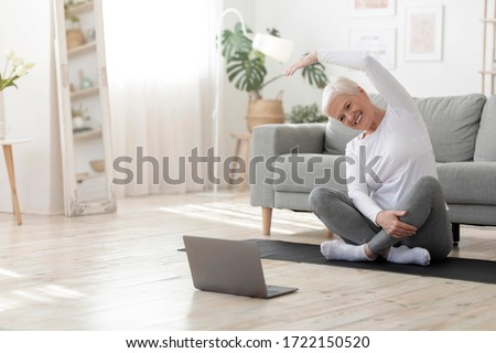 Sport In Mature Age. Happy senior woman doing stretching exercises in front of laptop at home, watching online tutorials, free space