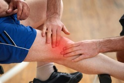 Sport injury at fitness club. Fitness trainer helps to man with injured knee at sport activity. Training and medical concept.