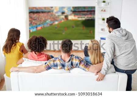 sport, leisure and entertainment concept - friends or football fans watching soccer game on projector screen at home #1093018634
