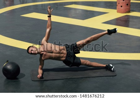 Sport man doing side plank exercise, fitness workout at gym. Male athlete with fit body exercising on yoga mat, planking outdoors on street