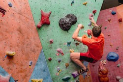 Sport man exercising on artificial climbing wall, modern leisure concept