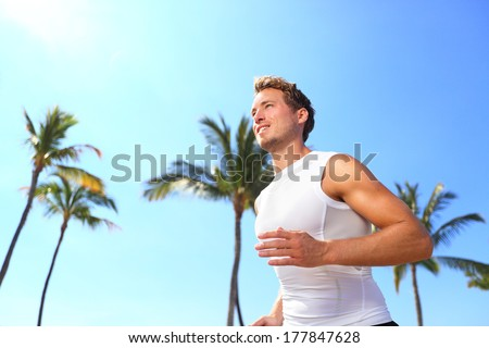 Sport man running Male athlete runner jogging in compression t-shirt top training on palm trees beach Fit handsome male fitness model jogging alone training for marathon run Man in his twenties