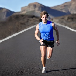 Sport man running. Runner sprinting training for marathon. Young strong male fitness model during run outdoors in beautiful landscape.