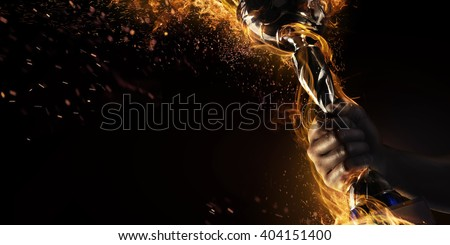 Sport. Man's hand holding up trophy goblet. Winner in a competition. Fire and energy