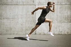 sport man starting running. Young man jogging front cement wall