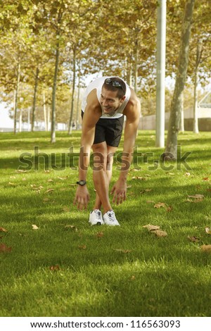 sport man stretching at the park - fitness concepts / Young man sports exercises.