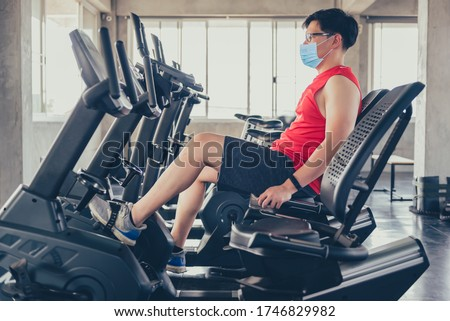 Sport man wear face mask for work out. Exercise bike at fitness gym. Social distancing and wellness. Fit and firm for healthy. Mind-body improvements. New normal and life after COVID-19.