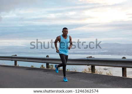 Sport, motivation and recreation concept. Active male sporty black jogger runs against cloudless sky in highway, wears casual vest and blue sportshoes, has biceps on arms, exercises outdoor.