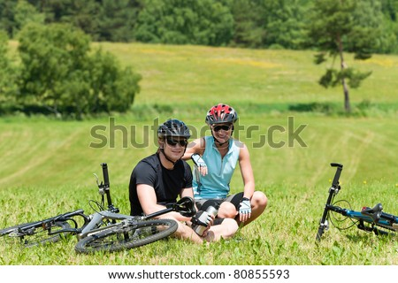 Sport mountain biking couple relax in meadows sitting drink water