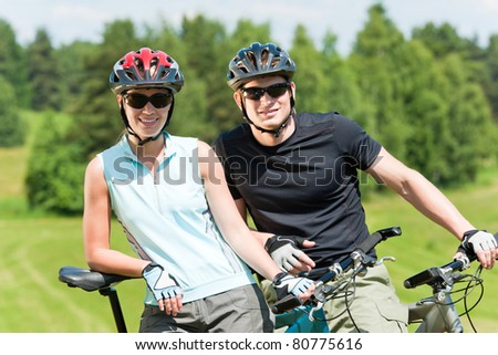 Sport mountain biking happy couple relax in meadows sunny countryside