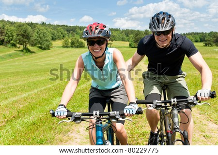 Sport mountain biking - man pushing young girl uphill sunny countryside - stock photo