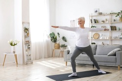 Sport On Retirement. Active Senior Woman Doing Pilates Workout At Home, Training In Living Room During Quarantine
