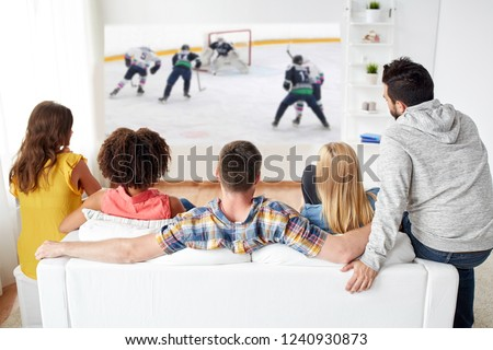 sport, people and entertainment concept - happy friends watching ice hockey game on projector screen at home