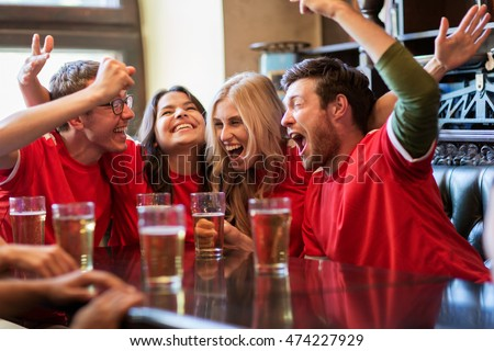 sport, people, leisure, friendship and entertainment concept - happy football fans or friends drinking beer and celebrating victory at bar or pub #474227929