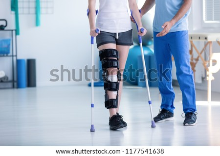 Sport physiotherapist and patient with leg injury during training with crutches Stock photo ©