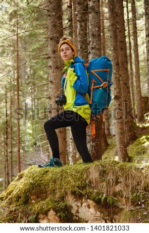 Sport, recreation and camping concept. Full legth shot of active female hiker overcomes long distance, dressed in comfortable clothes, carries big touristic backpack, photocamera, poses in forest #1401821033