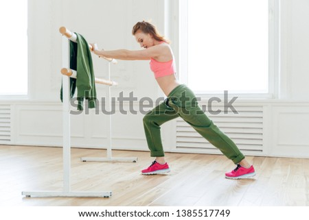 Sport, recreation, flexibility concept. Motivated strong female makes plank, leans at ballet barre, stretches before exercises prepares muscles or biceps for hard training. Aerobics instructor indoor #1385517749