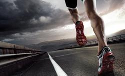 Sport. Runner feet running on road closeup on shoe.
