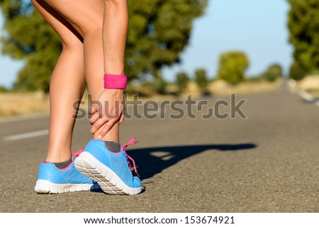 Sport running ankle sprain. Sportswoman touching painful twisted or broken ankle. Athlete runner training accident.