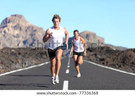 Sport running. Male Runners on road in endurance run outdoors in beautiful landscape - two men. - stock photo